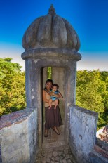 woman and baby sit in an archery tower of a castle - Sintra, Portugal
