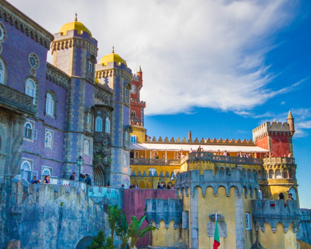 A castle with multi-coloured facade stands against a blue mountain sky - Sintra, Portugal