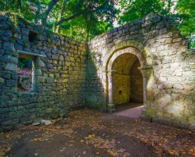A ruined chapel sits in the woods and is lit up by sunlight through breaks in the trees - Sintra, Portugal