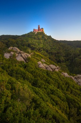 A colourful palace sits on a mountain top surrounded by forests - Sintra, Portugal