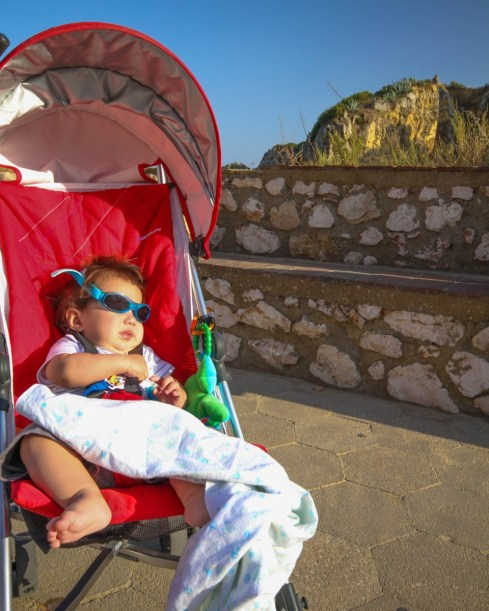 Baby with sunglasses on sits in a stroller at the beach - helping kids find nap time on the road
