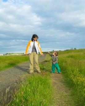 mother and young boy reach for each other while walking through a field