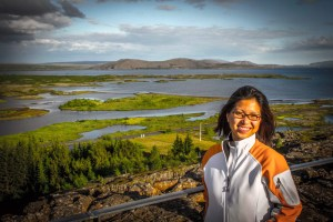 Asian woman looking at camera with Icelands Thingvellir National Park in the background - Iceland's Golden Circle