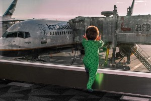 Young wearing pajama's boy looks out the window of an airport at an airplane - Iceland's Golden Circle