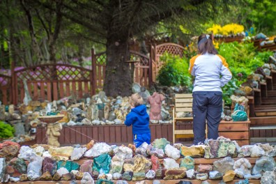 a mother and young boy explore a quirky rock collection