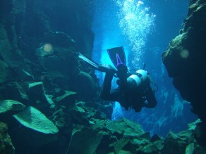 A SCUBA diver floats through narrow cracks in a fissure - Diving Iceland's Silfra
