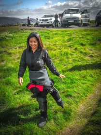 An asian woman wearing scuba attire walks through a field in iceland - Diving Iceland's Silfra