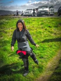 An asian woman wearing scuba attire walks through a field in iceland - Diving Iceland's Silfra