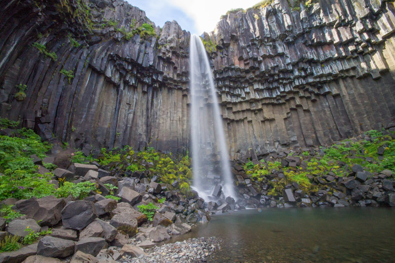 a waterfall dramatically falls over basalt columns in Iceland for kids