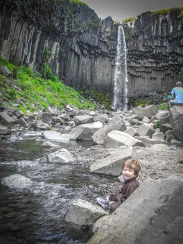 a young boy plays in a stream near a dramatic waterfall