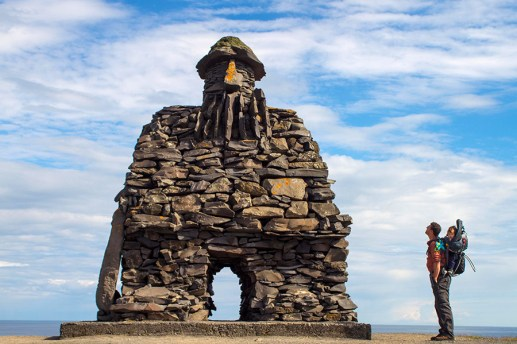 A father with his child in a backpack look at a massive viking statue