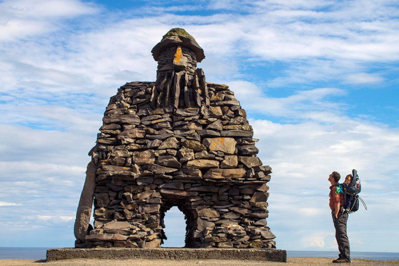 A father with his child in a backpack look at a massive viking statue Bardur in Iceland for kids