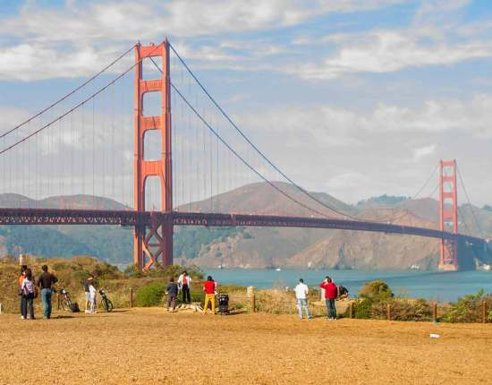 people walk along the coast below the Golden Gate Bridge in San Fancisco