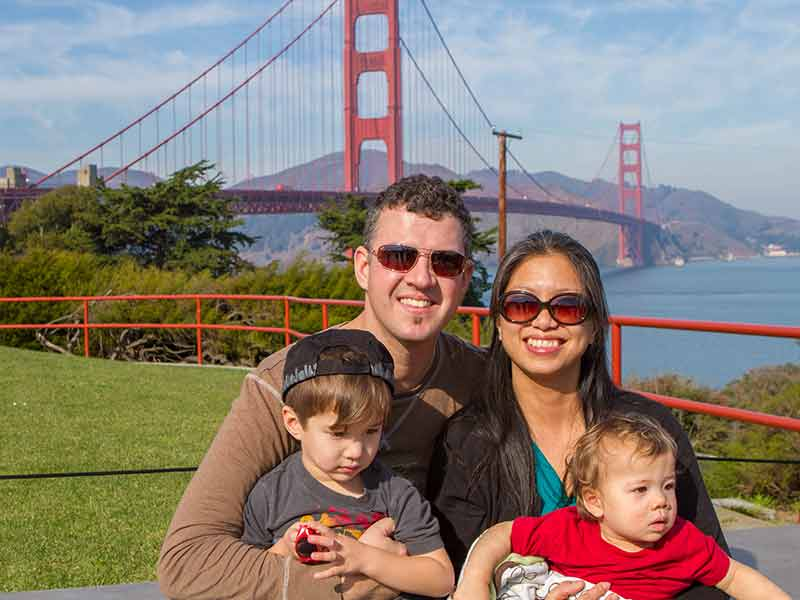 A young interacial family smiling in front of the Golden Gate Bridge in San Francisco