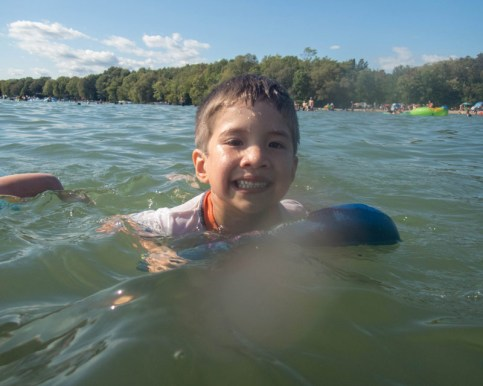 A young boy swims with the help of a board in a lake while camping in Mara Provincial Park with kids