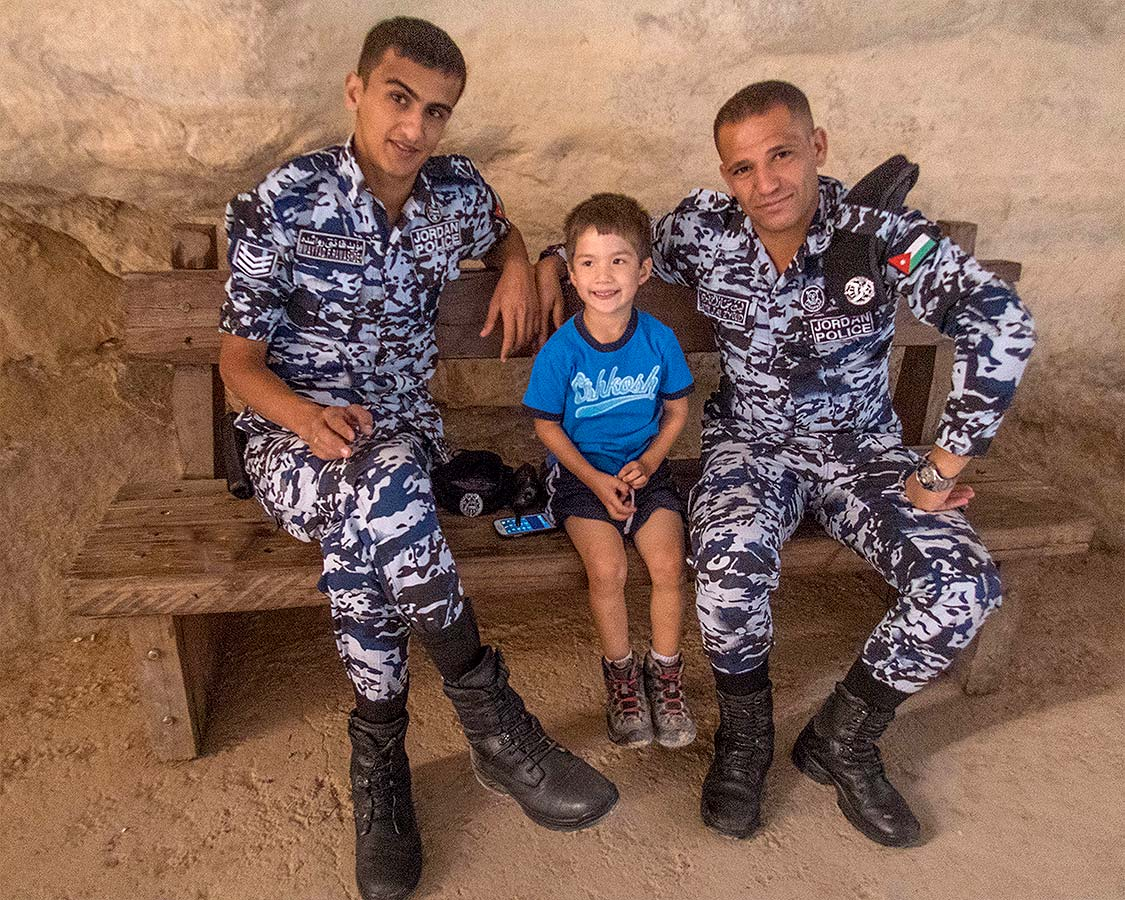 Boy poses with two Jordanian Police officers