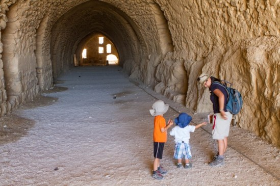 Woman and two young children explore a castles tunnels