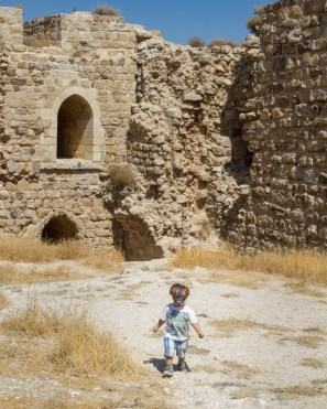 Toddler explores the courtyard of an ancient castle