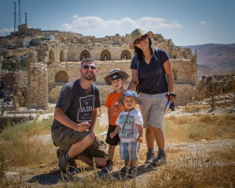Family of four pose in the ruined courtyard of an ancient castle