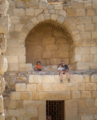 Father and two young boys sit on the walls of a castle