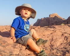 Toddler sits on a rock in the desert