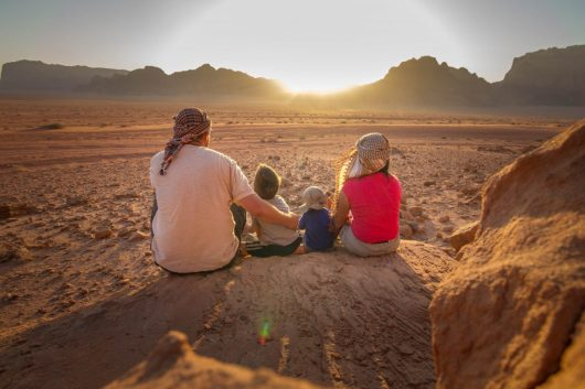 A family of four watches the sunset in Wadi Rum