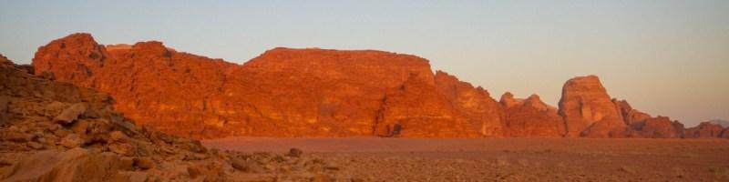 Panoramic view of hte sun lit red rocks of Wadi Rum