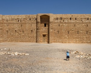 Toddler walks alone towards a castle in the desert - Traveling Jordan with Kids