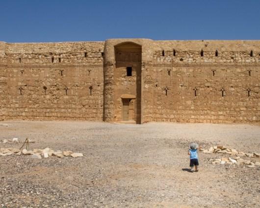 Young boy walking in front of Al Kharaneh Castle