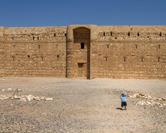 Young boy walking in front of Al Kharaneh Castle