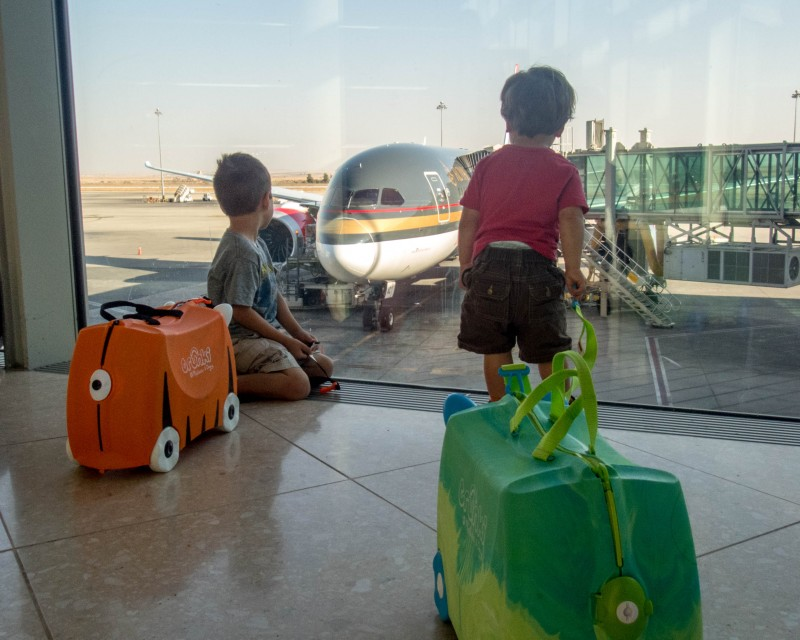 Two young boys with colourful luggages look out the window of an airport at an airplane - Traveling Jordan with Kids