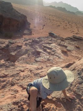 Young boy scrambles up rocks in the desert