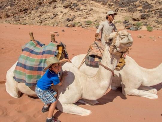 Young boy hugs a camel in Wadi Rum