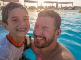 Father and son splashing in a pool in the Radisson Blu Resort near the Red Sea, Jordan.