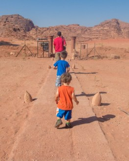 Father and two sons walk along a path towards a truck in the desert