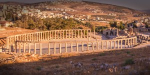 A ring of columns at Umm Qais in Jordan with the city in the background