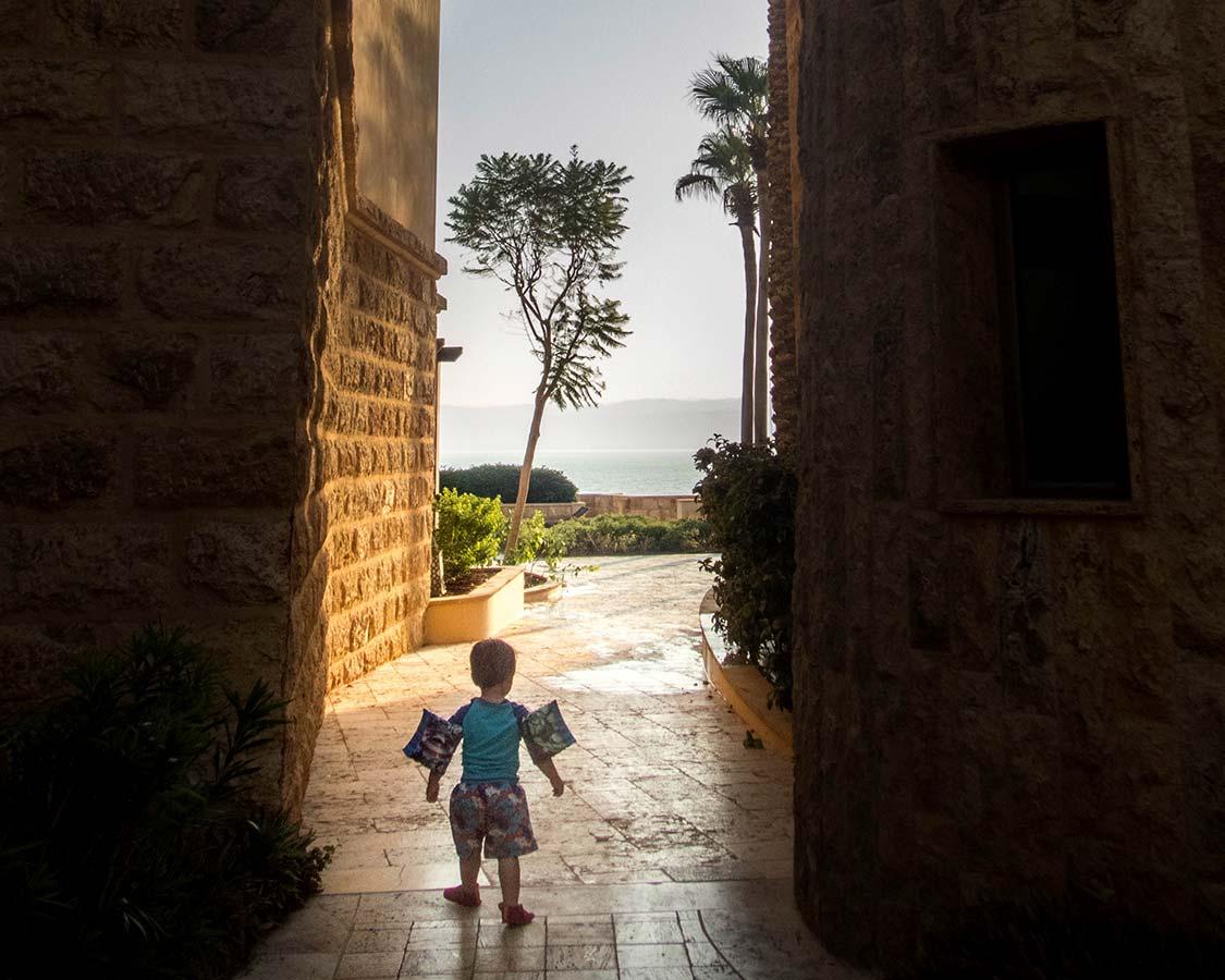 Toddler walking to the water at the Kempinski Ishtar Dead Sea Resort Jordan