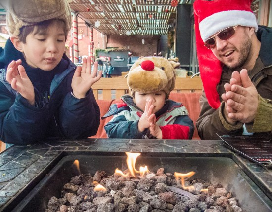 Father and sons in front of a fire at the Toronto Christmas Market