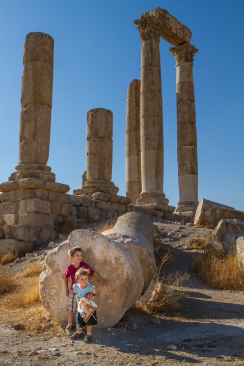 Children near a fallen pillar at the temple of Hercules in Jordan