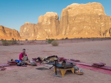 Father and son sit by a campfire in Wadi Rum
