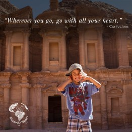 Boy smiling and pulling on his hat in front of the ruins of Petra