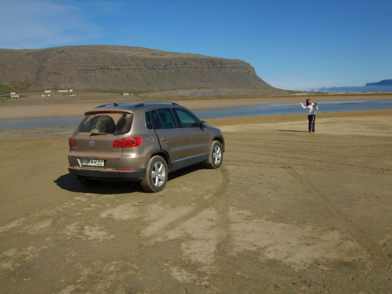 A woman stands on a beach near her SUV as she explores Iceland for kids