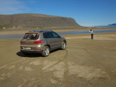 A woman stands on a beach near her SUV