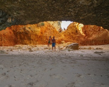 Men in a cave on a beach