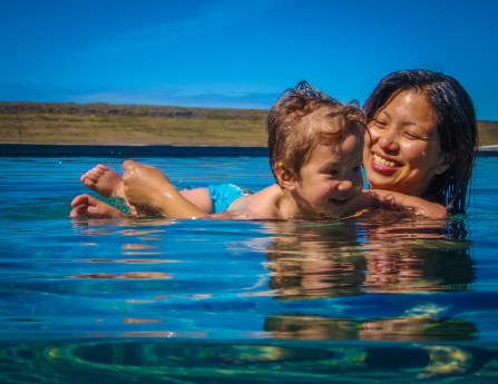 Mother and young boy practice swimming in an outdoor pool