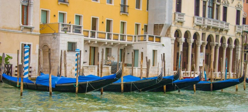 Gondolas parked in a line next to colourful buildings in Venice, Italy - Lost in Venice