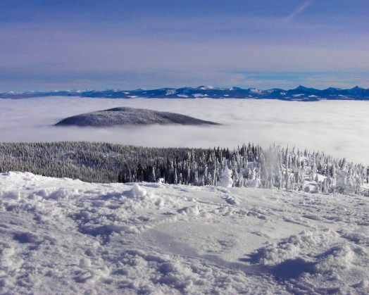 A mountain top peaks out above the clouds - Learning to ski at Kelowna's Big White