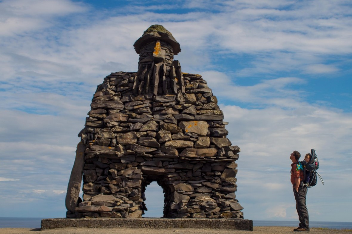 Man with child in a kid carrier check out a stone viking monument in Iceland
