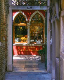 Shop wit arched windows and bright pain at the end of an alley in Venice, Italy - Lost in Venice
