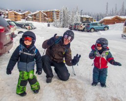 Dad and two young boys wearing ski gear - Learning to Ski at Kelowna's Big White